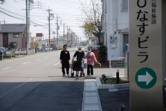 入居者と一緒に、外でシルバーカーで歩行訓練する職員